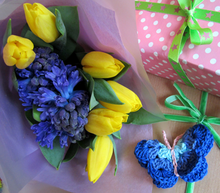 a bouquet of yellow tulips, blue hyacinths and birthday presents