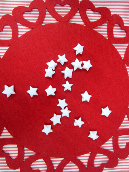 white origami stars on red Origami Stars -  Day three Planet Penny Advent Calendar