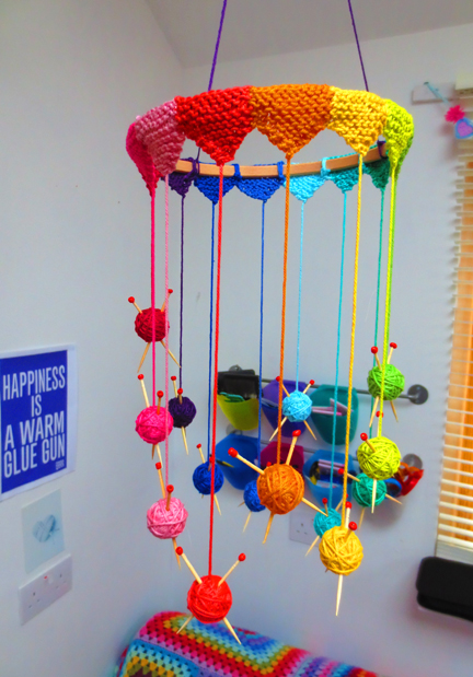 A mobile of mini yarn balls and needles