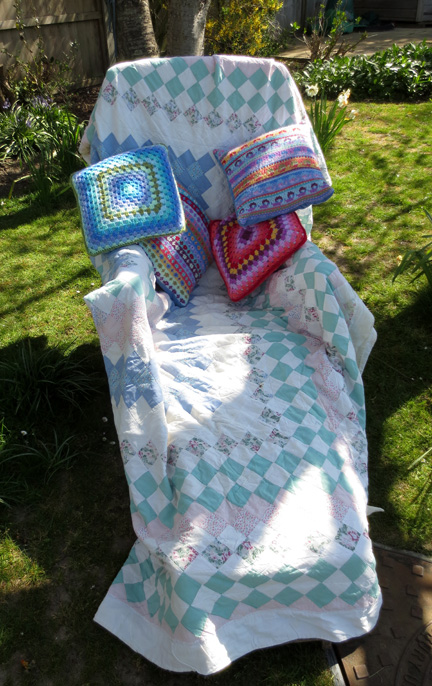 Patchwork Throw, crochet and knitted cushions in garden chair the place to Switch Off